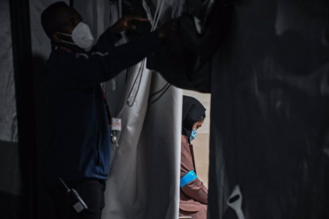FILED - 20 August 2021, Brandenburg, Doberlug-Kirchhain: An Afghan woman sits in a tent after arriving at the grounds of the German Red Cross (DRK) Refugee Aid at the Initial Reception Centre early in the morning. The evacuation of foreigners and Afghan c
