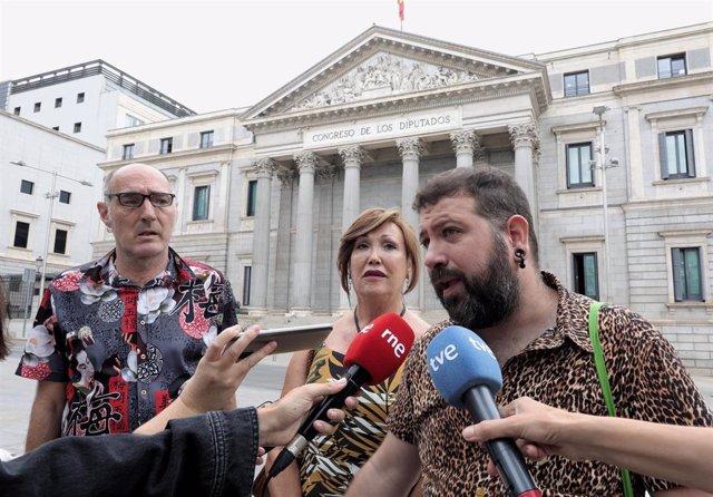 El presidente del Observatorio Contra la Homofobia de Cataluña, Eugeni Rodríguez; la presidenta de la Plataforma Trans, Mar Cambrollé; y el representante del Observatorio Contra la LGTBI+fobia de Vitoria-Gasteiz, Amets Martínez delante del Congreso.