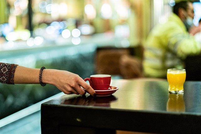 Archivo - Una trabajadora lleva un café.