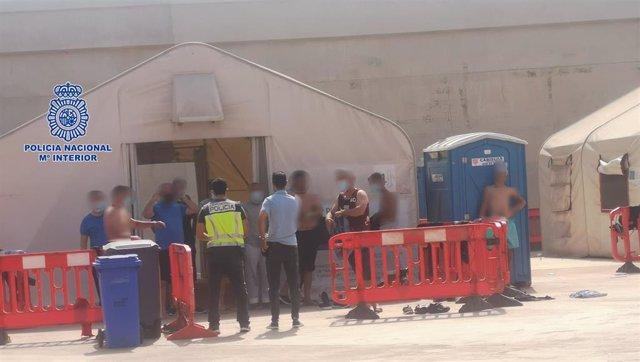 Personas en situación irregular llegadas a la costa murciana en pateras esperan en el muelle de Escombreras (Cartagena)