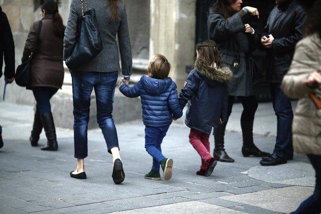Archivo - Una madre paseando con sus hijos.