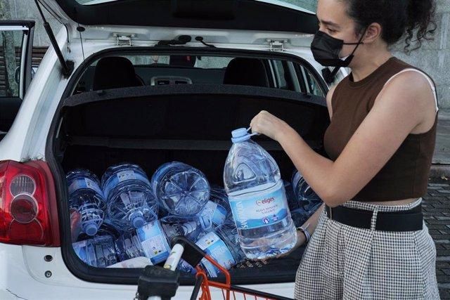 Una mujer carga con varios bidones con agua, a 11 de septiembre en Santiago de Compostela, A Coruña (Galicia).