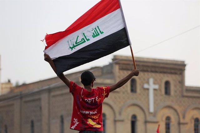 Archivo - Un manifestante sostiene una bandera en la plaza Tahrir de la capital iraquí de Baghdad, durante las protestas de 2019 contra el Gobierno.