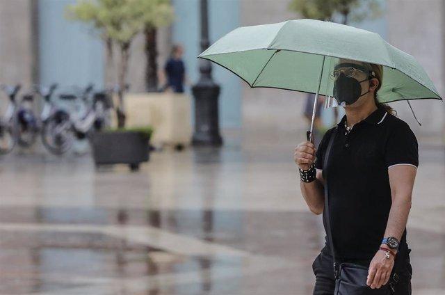 Archivo - Una persona sostiene un paraguas mientras llueve, a 26 de julio de 2021, en Valencia, Comunidad Valenciana, (España).