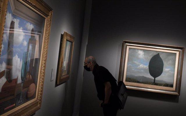 Una persona observa una de las obras de la exposición 'La máquina de Magritte' en el Museo Nacional Thyssen-Bornemisza