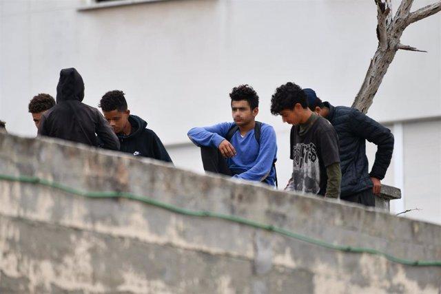 Varios menores migrantes, en el tejado de una nave industrial, a 27 de agosto de 2021, en Ceuta, (España).