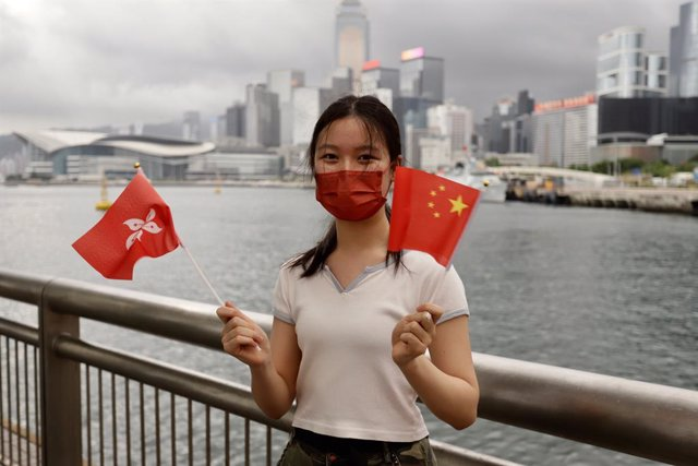 Archivo - 01 July 2021, China, Hong Kong: A young Chinese woman waves China's national flag and Hong Kong official flag as gesture of celebration at the Victoria Harbour waterfront on the morning of the 24th anniversary of Hong Kong's Handover and 100th a