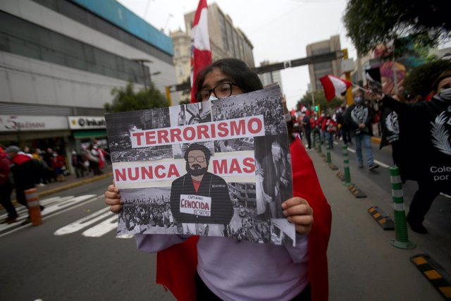 12 September 2021, Peru, Lima: A woman carries a placard describing Peruvian guerrilla leader Guzman as a mass murderer at a demonstration marking his death. Abimael Guzman, the former leader of the Peruvian guerrilla organization Shining Path (Sendero Lu