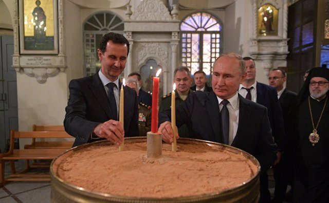 Archivo - HANDOUT - 07 January 2020, Syria, Damascus: Russian President Vladimir Putin (C) and Syrian President Bashar Assad light candles during their visit to the Mariamite Cathedral of Damascus. Photo: -/Kremlin/dpa
