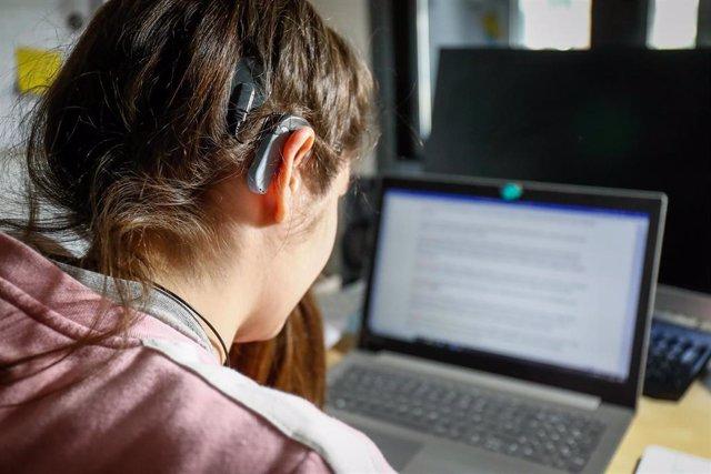 Archivo - Una joven usuaria de audífonos estudiando en su habitación.