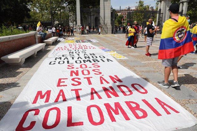 """Una pancarta donde se lee """"Nos están matando"""", en una manifestación contra la llegada del presidente de Colombia a Madrid, en la Puerta de Alcalá, a 12 de septiembre de 2021, en Madrid (España). Esta manifestación protesta contra la llegada del mandatario"""