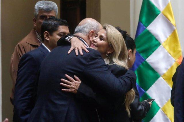 Archivo - Jeanine Áñez y su 'número dos', Arturo Murillo, se funden en un abrazo en la ceremonía de autoproclamación de ella.