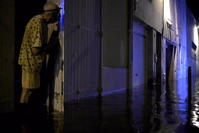 Un anciano observa las aguas de la inundación tras las fuertes lluvias