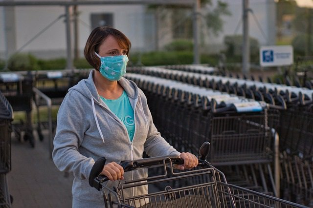 Archivo - Mujer a la salida de un supermercado con carro de la compra. Mascarilla de tela.