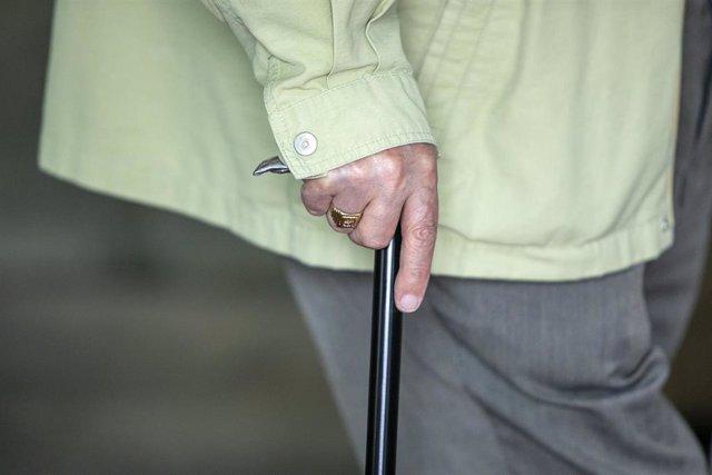 Archivo - Un anciano camina ayudado de un bastón.