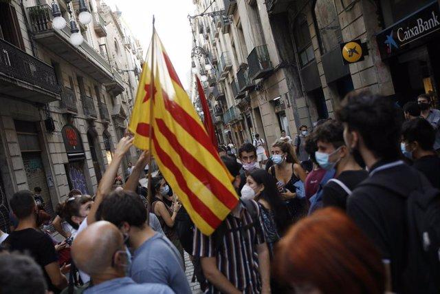 Diverses persones amb banderes de l'Estelada, durant una protesta convocada per la CUP i altres organitzacions de l'esquerra independentista contra la taula del diàleg entre el Govern central i el Govern català a la plaça de Sant Jaume de Barcelona,
