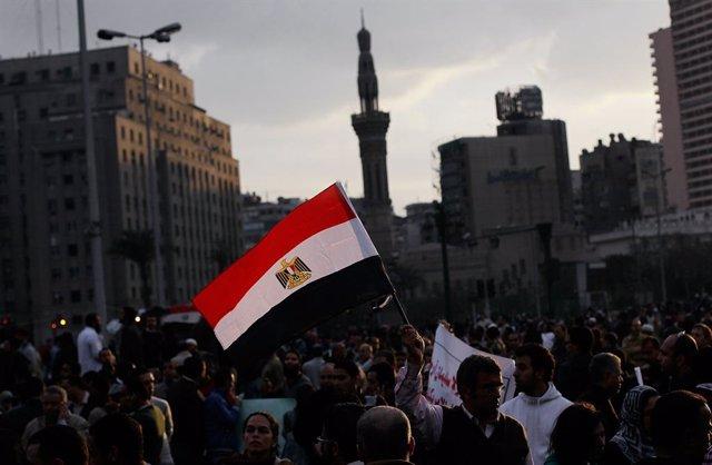 Archivo - Un hombre sostiene una bandera egipcia mientras el sol se pone en una protesta masiva antigubernamental en la Plaza Tahrir el 30 de enero de 2011 en El Cairo.
