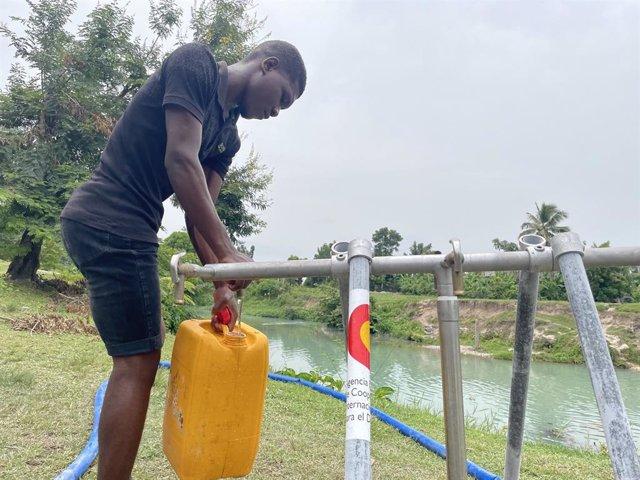 Un hombre en un punto de aprovisionamiento de agua instalado con ayuda de AECID en Haití