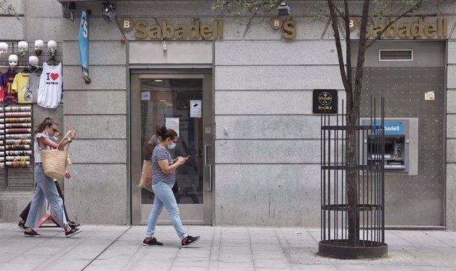 Varias personas pasan por una sucursal de Banco Sabadell, a 2 de septiembre de 2021, en Madrid (España). Banco Sabadell ha propuesto a los sindicatos un plan de ajuste de su plantilla que contempla el despido de 1.900 empleados.