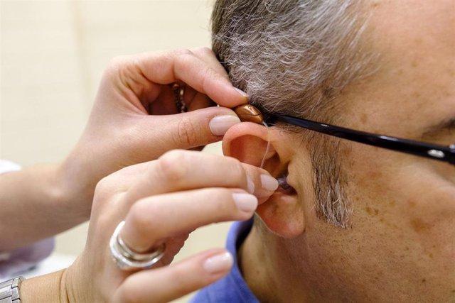 Archivo - Especialista haciendo una prueba de audífono