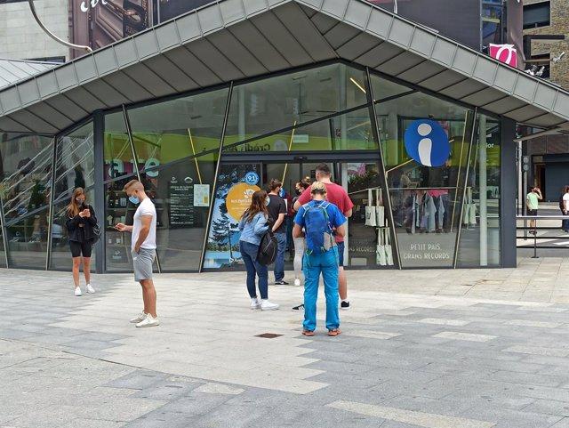 Turistes i excursionistes fan cua per entrar a l'oficina d'informació turística d'Andorra la Vella