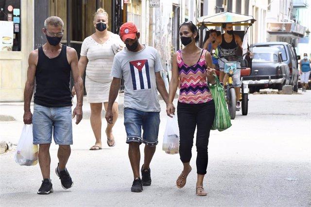 Personas con mascarilla en una calle de La Habana