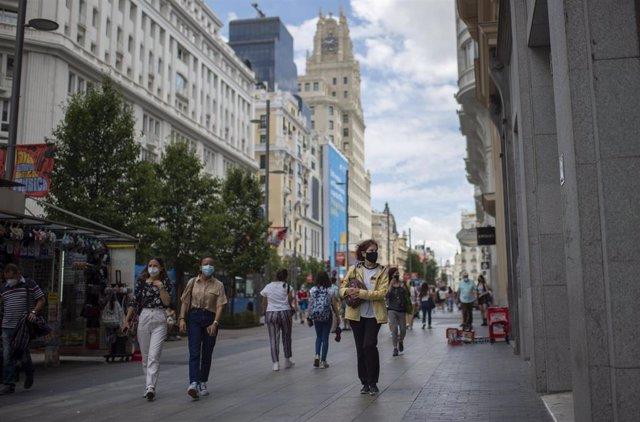 Archivo - Varias personas caminan por la Gran Vía con mascarilla.