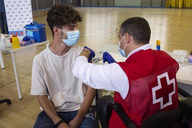 Un voluntario de Cruz Roja administra una dosis de la vacuna contra el Covid-19 a un estudiante universitario en el campus de Ciudad Universitaria, a 14 de septiembre de 2021, en Madrid, (España).