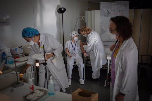 Archivo - Arxivo - Una infermera bovina a un professional sanitari amb la vacuna de Pfizer-BioNtech contra el COVID-19 a l'Hospital de la Santa Creu i Sant Pau de Barcelona, Catalunya (Espanya), a 14 de gener de 2021. Fa deu dies que es va començar en la
