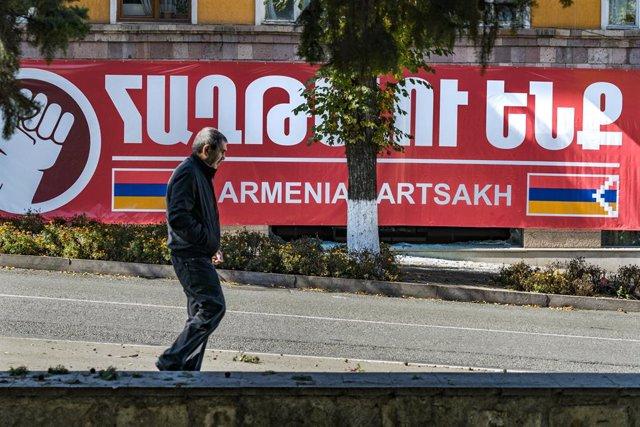 Archivo - Un hombre camina por una calle de Stepanakert, capital de Nagorno Karabaj, cerca de un cartel con la bandera armenia y de Artsaj, como se conoce en Armenia a Nagorno-Karabaj