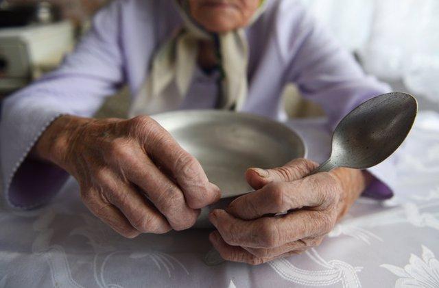 Archivo - Manos de mujer mayor sujetando un plato de comida. Anciana. Comer. Desnutrición.