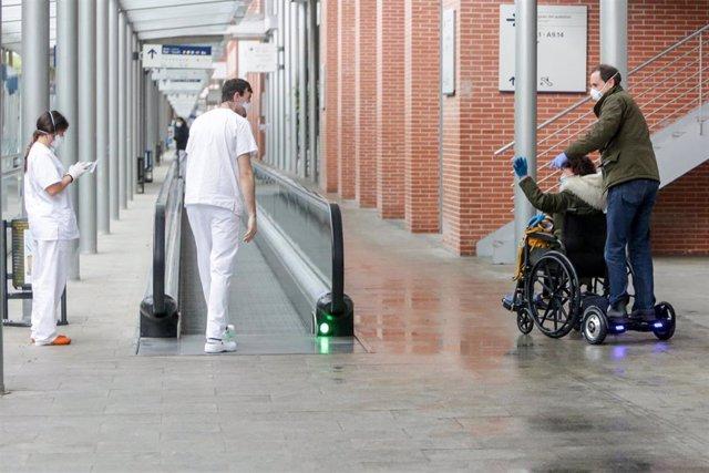 Archivo - Dos sanitarios protegidos con mascarillas y guantes saludan a una paciente en silla de ruedas.