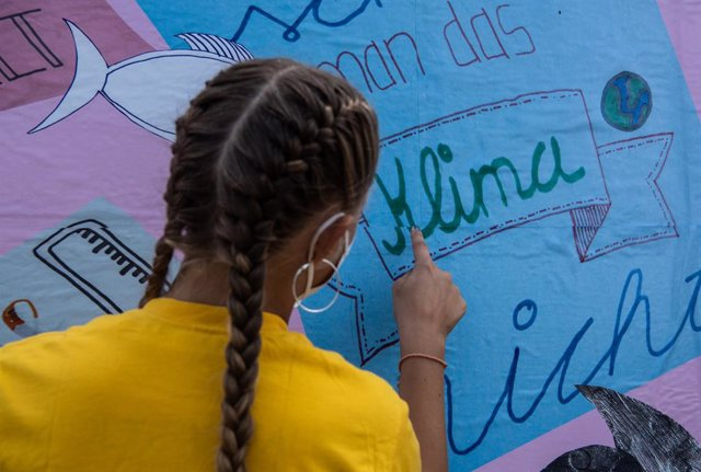 """Archivo - 30 July 2021, Berlin: A young environmental activist puts up an election poster in front of the German Reichstag building to mark the start of the """"vote4me"""" children's campaign called by the environmental protectIon organisation Greenpeace. Phot"""