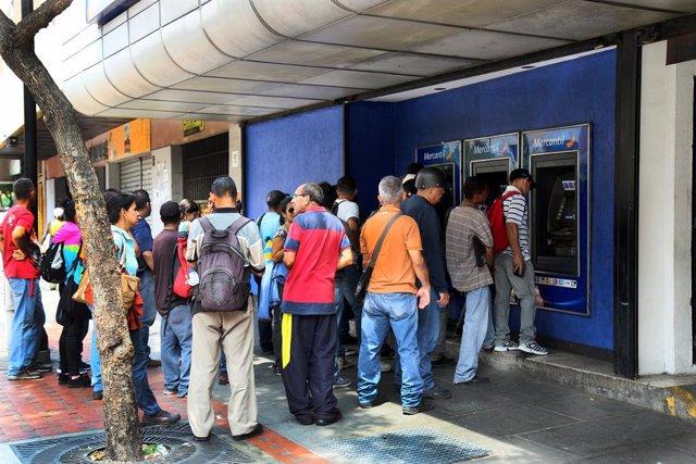 Archivo - La gente hace cola frente a un cajero automático en Venezuela
