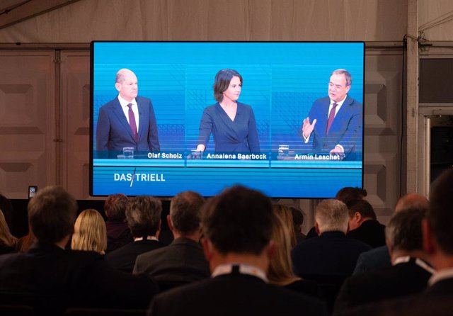 12 September 2021, Berlin: People look at a screen during a TV discussion for chancellor candidates on ARD and ZDF between (R-L) Armin Laschet, Minister President of North Rhine-Westphalia and candidate for chancellor of the Christian Democratic Union (CD