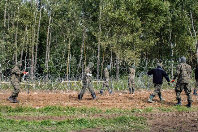 01 September 2021, Poland, Wojnowce: Polish soldiers build a razor-wire fence along the border with Belarus close to the village of Minkowce. The Polish government is introducing a State of Emergency on the border with Belarus in two voivodeships (the hig
