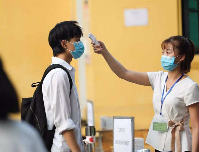 Un joven se somete a un control de temperatura en un centro escolar de Hanói.