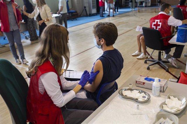 Una voluntaria de Cruz Roja administra una dosis de la vacuna contra el Covid-19 a un estudiante universitario en el campus de Ciudad Universitaria, a 14 de septiembre de 2021, en Madrid, (España).