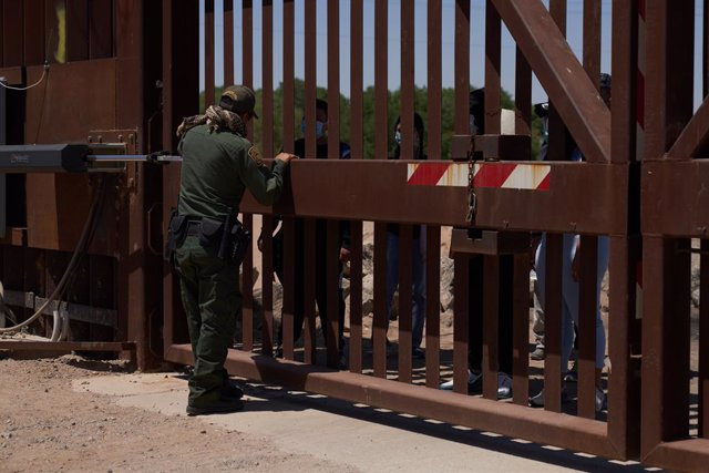 Archivo - 23 April 2021, US, Yuma: Asylum seeking migrants surrender to United States Border Patrol at the US Border Wall with Mexico in Yuma. Photo: Allison Dinner/ZUMA Wire/dpa