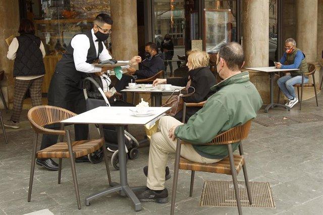 Archivo - Un camarero atiende a varios clientes en la terraza de un bar en Palma.