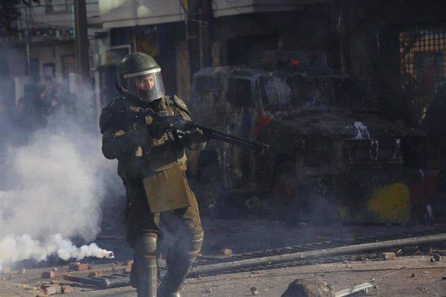 Archivo - Un agente de Carabineros con una escopeta antidisturbios en medio de gases lacrimógenos durante una protesta en Concepción en noviembre de 2019