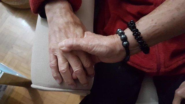 Pilar coge la mano de Valentín, su marido, que tiene Alzheimer.