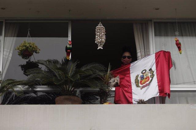 Archivo - Una vecina de Lima alienta a sus vecinos desde el balcón de su casa con una bandera de Perú.