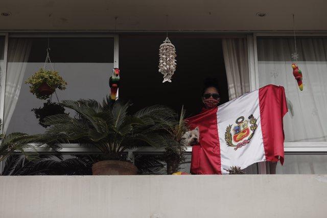 Archivo - Una vecina de Lima alienta a sus vecinos desde el balcón de su casa con una bandera de Perú