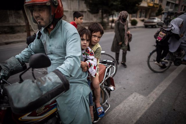 22 September 2021, Afghanistan, Kabul: An Afghan man rides a bike with his children. Photo: Oliver Weiken/dpa
