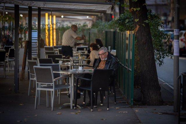 Archivo - Arxiu - Un home llegeix en una terrassa durant el primer dia de desescalada de la segona onada del coronavirus