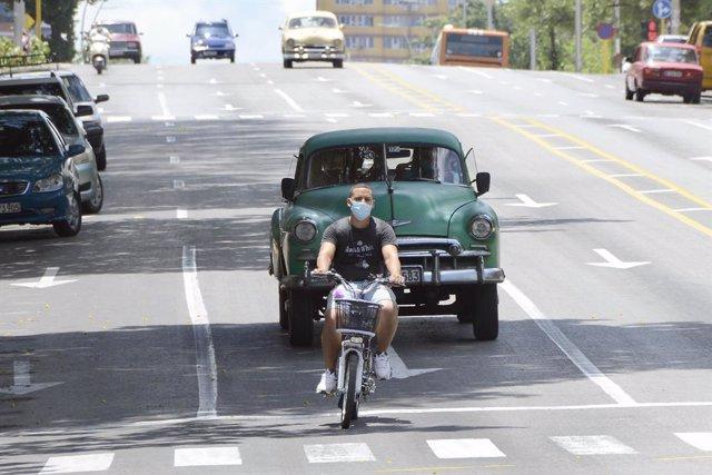 Archivo - Un ciclista con mascarilla en La Habana, Cuba