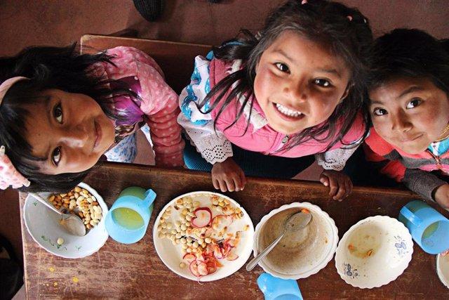 Archivo - Unas niñas comiendo en una escuela en Ecuador