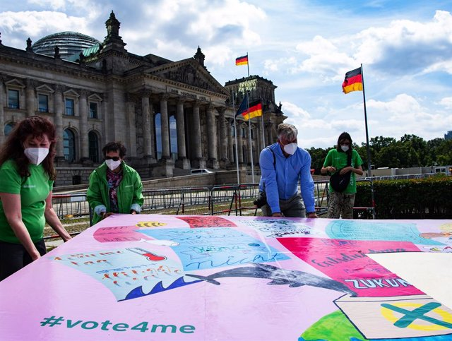 """Archivo - 30 July 2021, Berlin: Environmental activists put up election posters in front of the German Reichstag building to mark the start of the """"vote4me"""" children's campaign called by the environmental protectIon organisation Greenpeace. Photo: Paul Zi"""