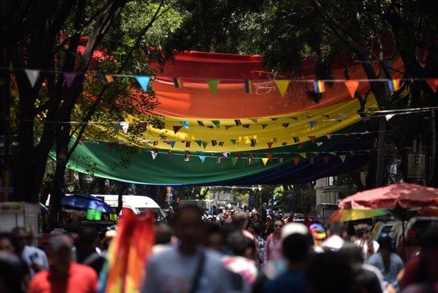 Archivo - La gente camina bajo una gran bandera arcoíris durante el Desfile del Orgullo LGBT en Ciudad de México 2019.